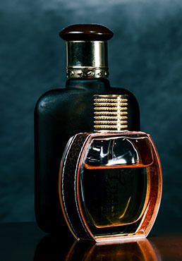 Romantic pair of glass  scent bottles on a dark surface of the noble wood.