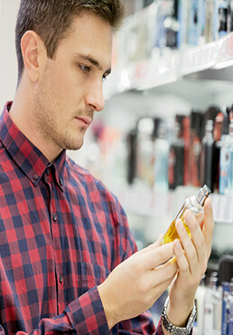 Man standing next to perfumes, holding perfume sample bottle
