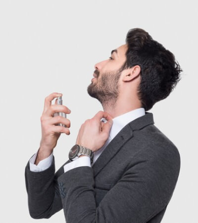 portrait-of-handsome-businessman-in-suit-applying-perfume-over-gray-picture-id930581644