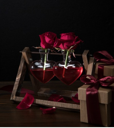 two-red-roses-in-heart-shaped-vases-on-wooden-stand-picture-id905988892